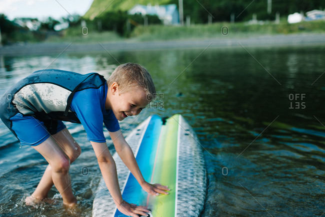 Boy leaning on a surfboard