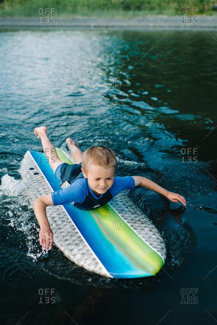 Boy paddling on a surfboard