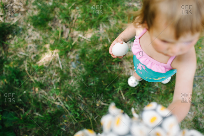 Little Girl holding a white egg