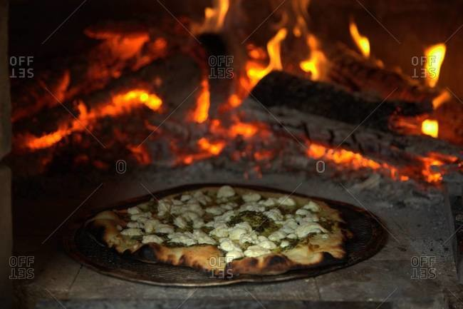 Making pizza in traditional wood-fired brick oven
