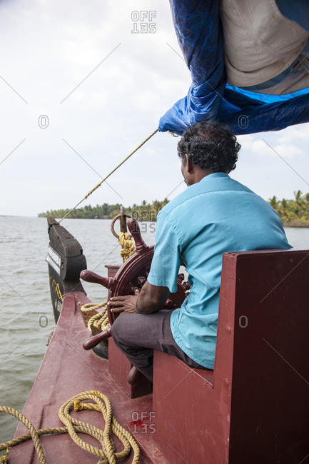 Rear view of Indian man sitting by a boat's wheel on a watercraft