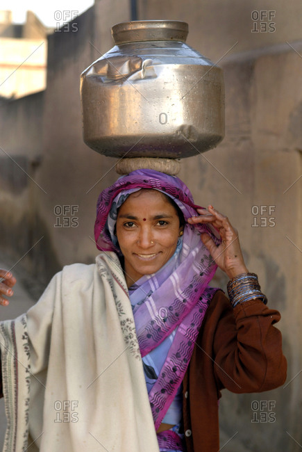 Bagar, India - December 25, 2006: Woman carrying a water pot on her head