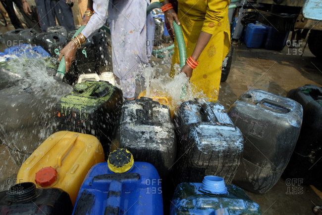 Indian woman washing out gas cans with hoses