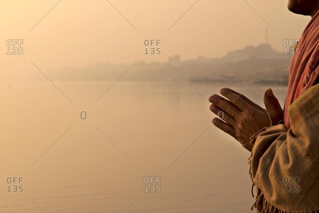 Hindu man praying on the riverside of Ganges in Varanasi, India