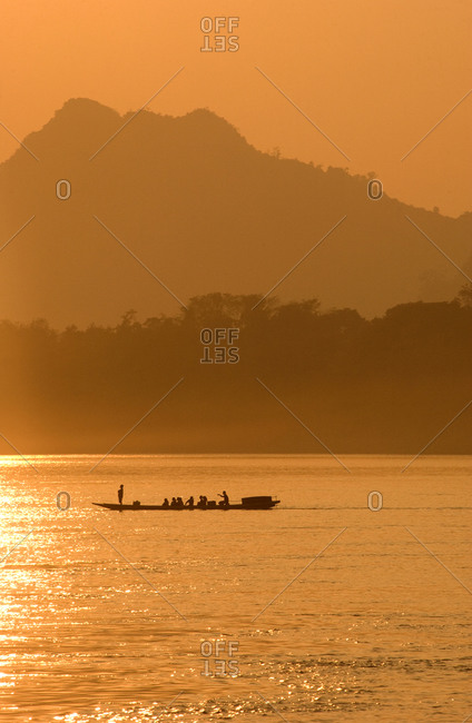 Boat on Mekong River at sunset in Luang Prabang, Laos