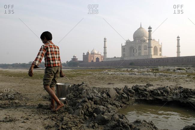 Boy carrying water nearby the Taj Mahal in Agra, India