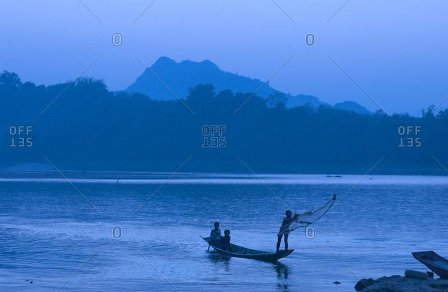 Children fishing on Mekong River at sunset in Luang Prabang, Laos