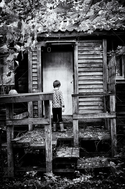 Child standing at the entrance of a cabin