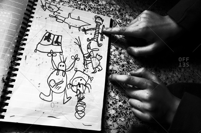 Kid showing his drawings in a notebook
