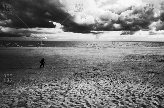 Child walking on a stormy beach