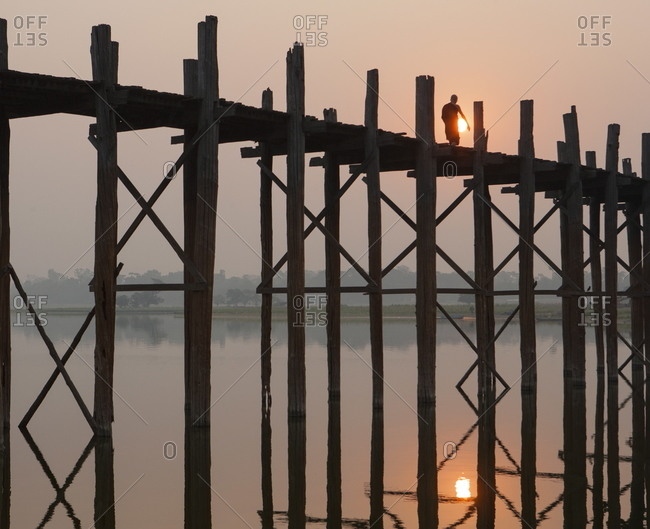 Reflection in water and Buddhist monk silhouetted at sunrise crossing U Bein teak bridge above Taungthaman Lake