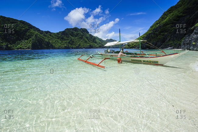 Outrigger boat in the crystal clear water in the Bacuit archipelago