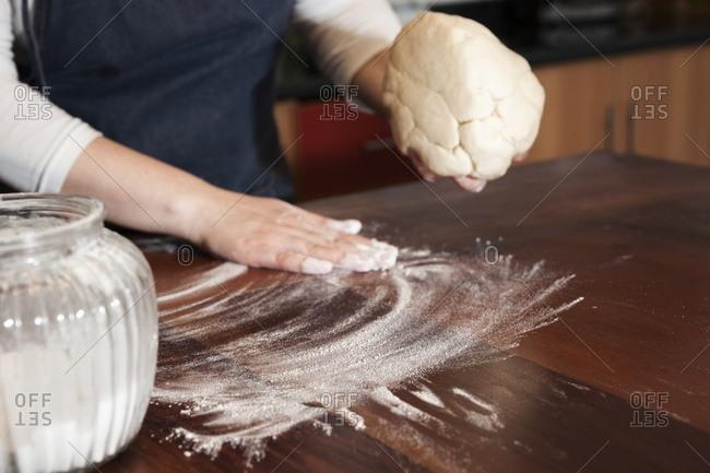 Spreading flour to roll dough for empanadas