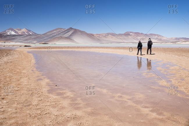 Two tourists walking along water at Miscanti Laguna