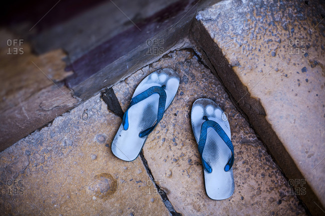 Old sandals worn through with footprints, Udaipur, India.