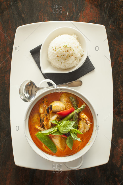 Tom yum served with rice on a table