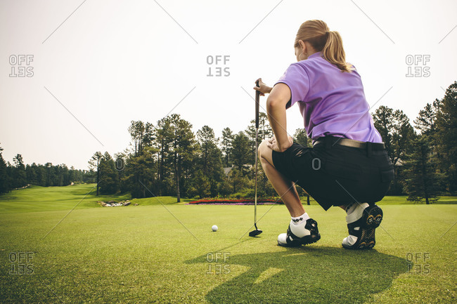 Woman lining up a putt at a golf course