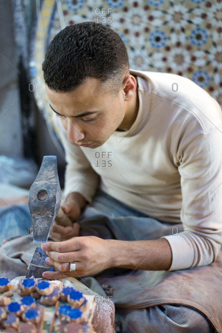 Fes el-Bali, Fes, Morocco - June 4,2013: A young Moroccan man cuts small intricate tiles in the art of zellige in a small factory in the old medina