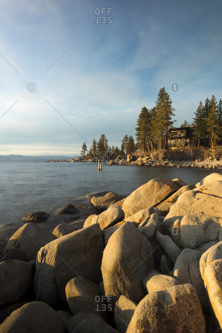 Sunset illuminates the shoreline of granite boulders on the east shore of Lake Tahoe, NV