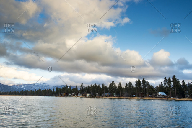 Looking back at the shoreline of Lake Tahoe from the popular Camp Richardson pier with clouds in the sky in South Lake Tahoe, California