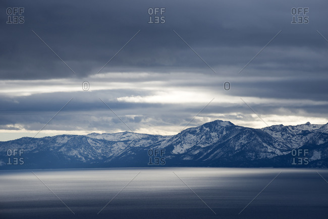 Light and storm clouds reflect off of Lake Tahoe over Mount Tallac with a winter storm on the horizon in Lake Tahoe, NV