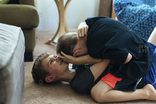 Twin boys wrestling on ground