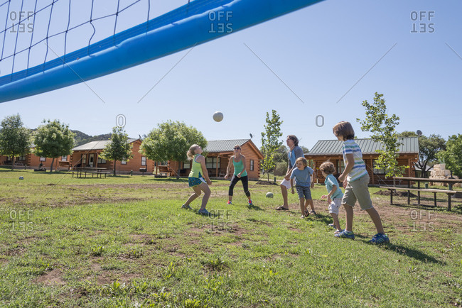 Family playing volleyball in grass