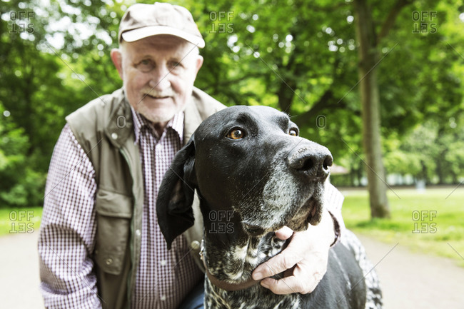Portrait of senior man with his German Shorthaired Pointer in city park