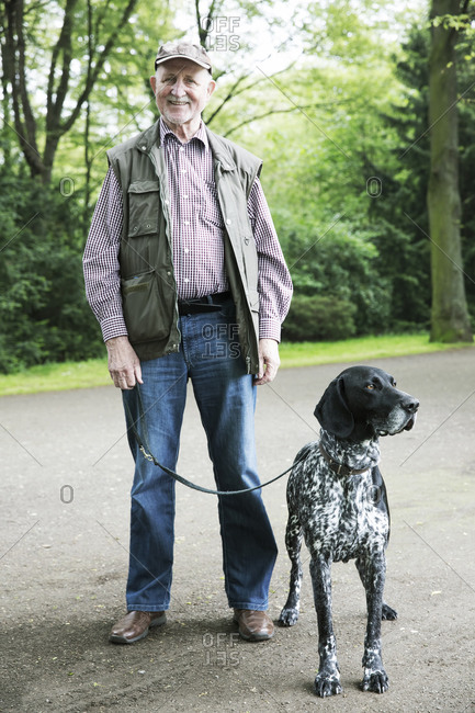 Senior man walking with his German Shorthaired Pointer in city park