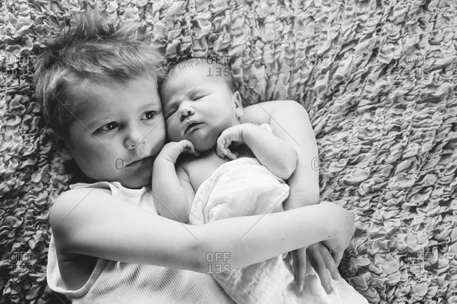 Boy hugging his baby sister