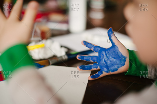 Child with blue paint all over his palm