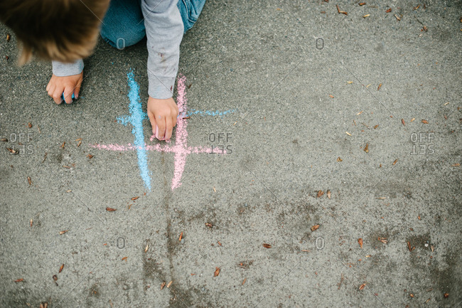 Overhead view of a kid drawing with chalk on an asphalt