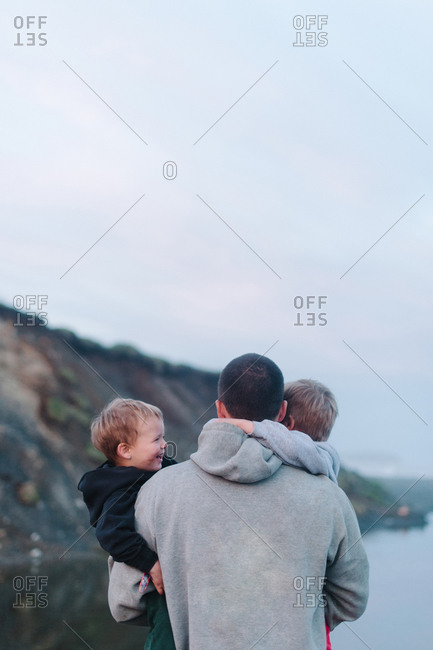 Rear view of father carrying his sons