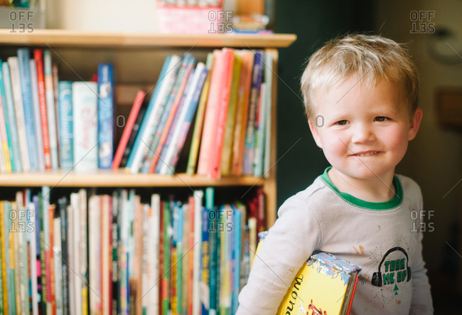 Half length of a boy standing with a storybook holding under his arm