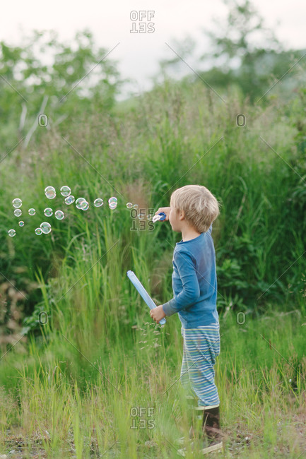 Boy blowing soap bubbles in the nature