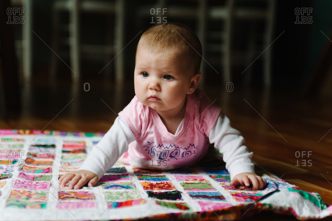Baby girl crawling on a patchwork blanket