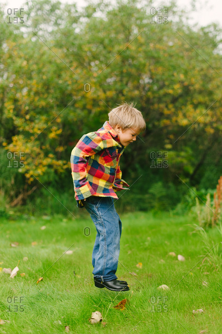 Side view of a boy jumping in the garden