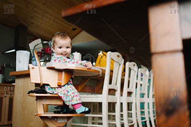 Child sticking her tongue out in a high chair