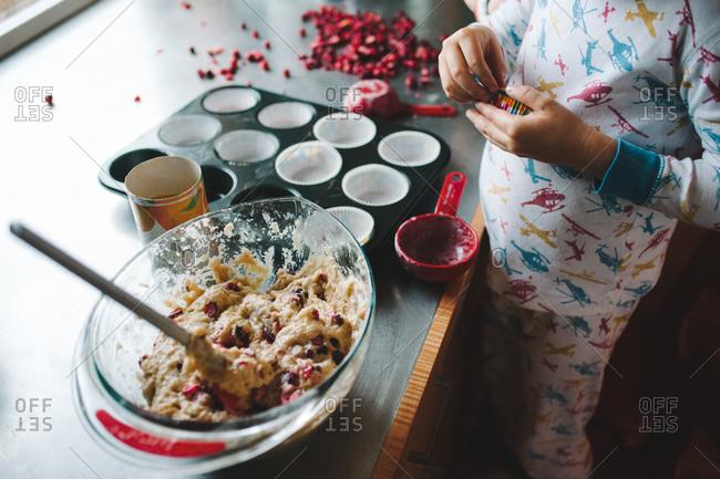 Boy making cranberry muffins