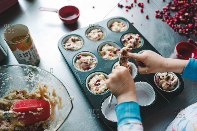 Boy filling up a muffin pan with cranberry dough