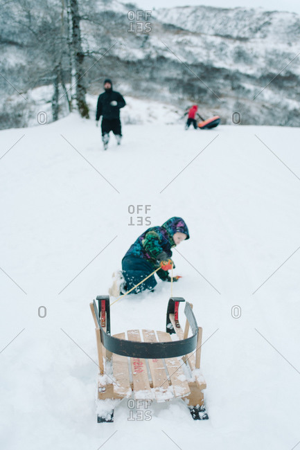 Child pulling a sled on snow
