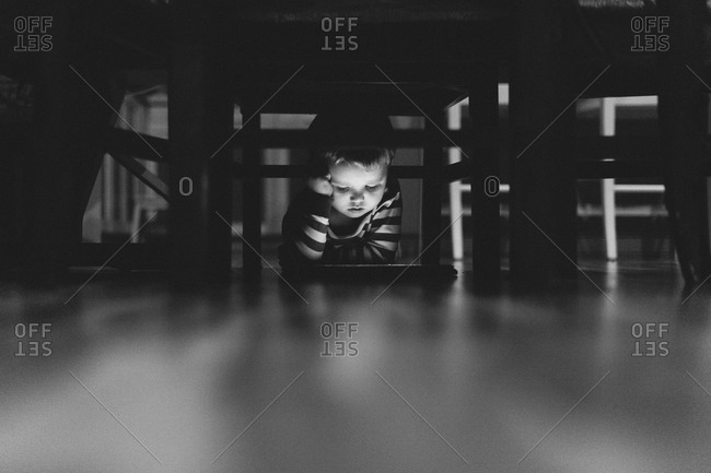 Boy looking at a tablet underneath a table