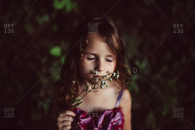 Girl smelling white flowers