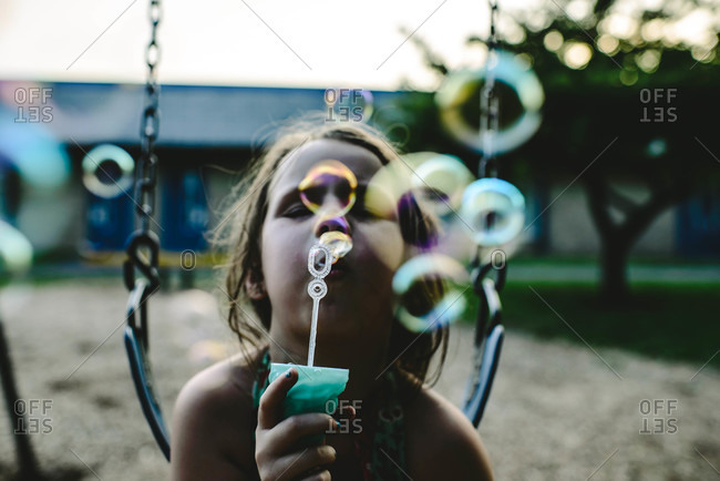 Girl blowing soap bubbles - Offset