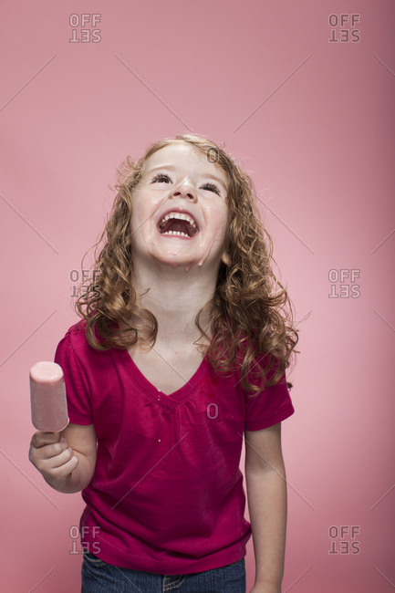 Little girl laughing and holding a fruity ice cream bar