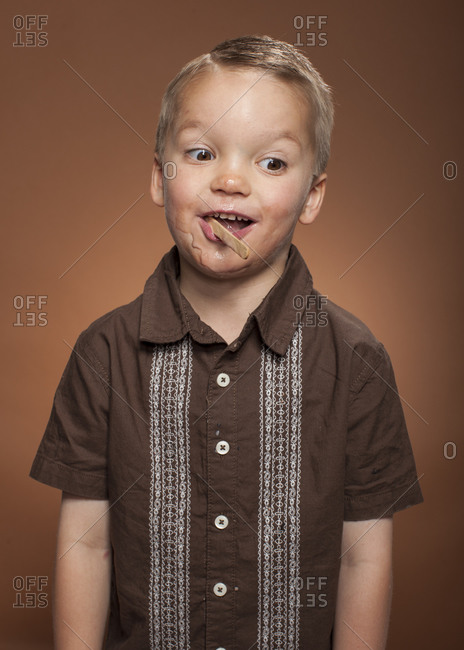 Boy standing with an ice cream bar stick in his mouth