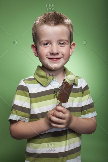 Redhead boy eating pistachio ice cream bar