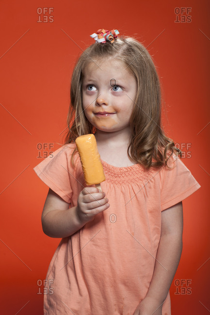Little girl standing with an ice cream bar