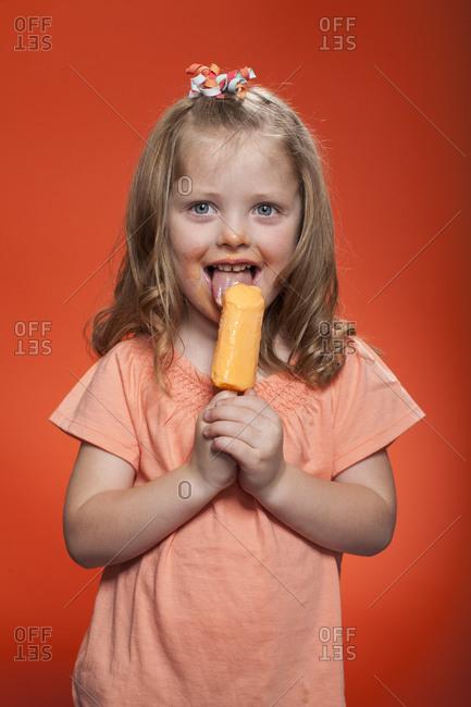 Little, long haired girl eating fruity ice cream bar