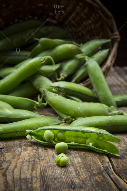 Green peas and peapods and basket
